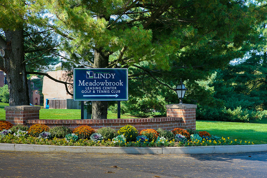 Sign at the entrance of Lindy Meadowbrook landscaped with flowers