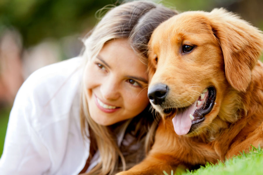 Young woman sitting with a golden retriever